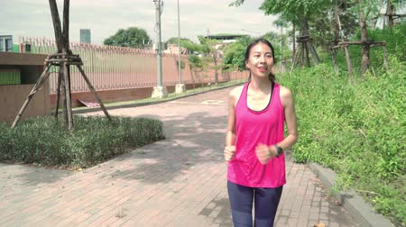 спринт : Healthy beautiful young Asian runner woman in sports clothing running and jogging on street in urban city park. Lifestyle fit and active women exercise in the city concept. Стоковые видеозаписи