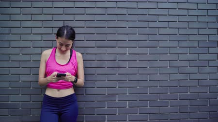 zweten : Healthy beautiful young Asian Athlete woman using smartphone for checking social media while relax after running in urban city. Lifestyle women exercise in the city concept.