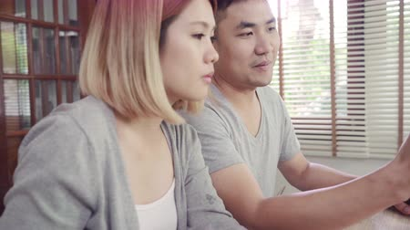 telefonda : Attractive young Asian couple distracted at table with newspaper and cell phone while eating breakfast. Excited young Asian couple surprised by unbelievably good news, happy family amazed by internet.