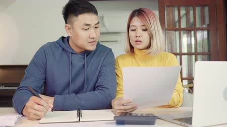 faktura : Young asian couple managing finances, reviewing their bank accounts using laptop computer and calculator at modern home. Woman and man doing paperwork together, paying taxes online on notebook pc. Dostupné videozáznamy