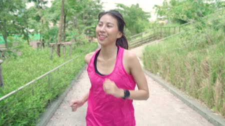 skok : Slow motion - Healthy beautiful young Asian runner woman in sports clothing running and jogging on street in urban city park. Lifestyle fit and active women exercise in the city concept.