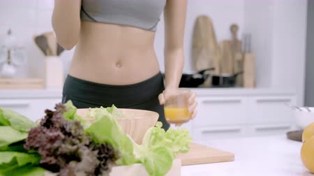 строгий вегетарианец : Young Asian woman drink orange juice making salad in the kitchen, beautiful female in sport clothing use organic fruits and vegetables making healthy food by herself at home. Healthy food concept. Стоковые видеозаписи