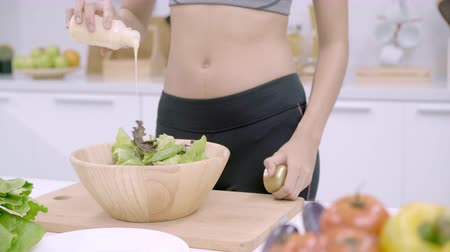 fehérjék : Young Asian woman making salad healthy food in the kitchen, beautiful female in sport clothing use organic vegetables lots of nutrition preparing salad for fit body at home. Healthy food concept.