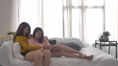 сестры : Slow motion - Beautiful young asian women LGBT lesbian happy couple sitting on bed hug and using phone together bedroom at home. LGBT lesbian couple together indoors concept. Стоковые видеозаписи
