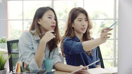 masaüstü : Attractive smart creative Asian business women in smart casual wear working on desktop while sitting on desk in office. Women work at office concept. Stok Video