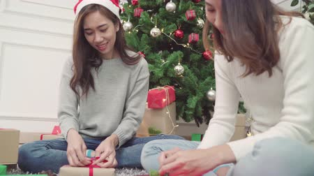 азиаты : Asians packing and wrapping Christmas present to decorate living room at home in Christmas Festival.