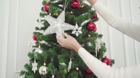 азиаты : Asians feeling happy decorating christmas tree in living room at home in Christmas Festival.
