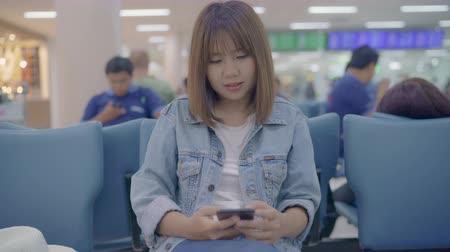 partenza : Happy Asian woman using and checking her smartphone while sitting on chair in terminal hall while waiting her flight at the departure gate in international airport. Women happy in airport concept. Filmati Stock