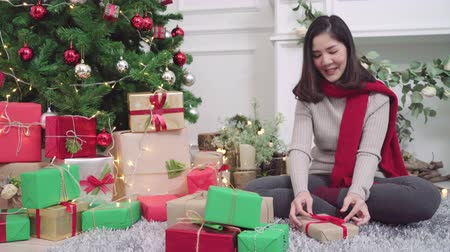confortável : Cheerful happy young Asian woman packing and wrapping Christmas present decorate her living room at home in Christmas Festival. Lifestyle woman celebrate Christmas and New year concept.