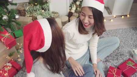 азиаты : Asians packing and wrapping Christmas present decorate living room at home in Christmas Festival. Стоковые видеозаписи