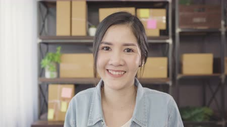 hírnök : Business woman feeling happy smiling and looking to camera while working in her office at home. Beautiful Asian young entrepreneur owner of SME with small business owner at home office concept.