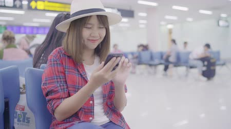 bavul : Happy Asian woman using and checking her smartphone while sitting on chair in terminal hall while waiting her flight at the departure gate in international airport. Women happy in airport concept. Stok Video