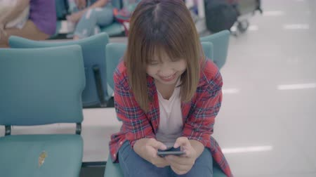 hátizsákkal : Happy Asian woman using and checking her smartphone while sitting on chair in terminal hall while waiting her flight at the departure gate in international airport. Women happy in airport concept. Stock mozgókép
