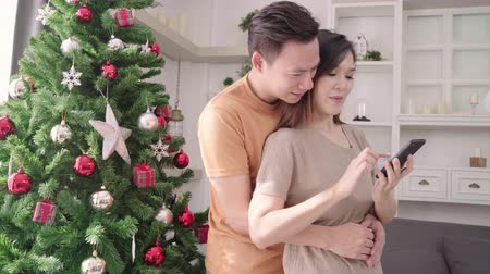 dinlenmek : Asian couple using smartphone selfie with christmas tree decorate their living room at home in Christmas Festival. Lifestyle woman and man happy celebrate summer christmas and New year concept.