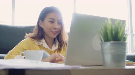 честолюбивый : Beautiful young smiling asian woman working on laptop and drinking coffee in living room at home. Asia business woman working document finance and calculator in her home office. Enjoying time at home.