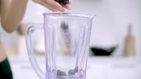 kitchen blender : Slow motion - Sporty Asian woman using blender to make grape juice in the kitchen, beautiful female in sport clothing use organic fruit lots of nutrition herself at home. Healthy food concept.