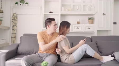 konfor : Asian couple using smartphone check social media in living room at home, sweet couple enjoy love moment while lying on the sofa when relax at home. Lifestyle couple relax at home concept.