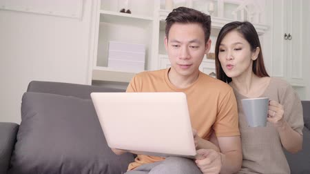 comfortable : Asian couple using laptop and drinking warm cup of coffee in living room at home, sweet couple enjoy love moment while lying on the sofa when relax at home. Lifestyle couple relax at home concept. Stock Footage