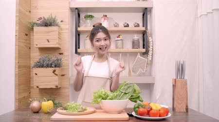 korejština : Blogger Asian woman using camera recording how to make salad healthy food video for her subscriber, female use organic vegetables preparing salad for fit body at home. Healthy food concept.