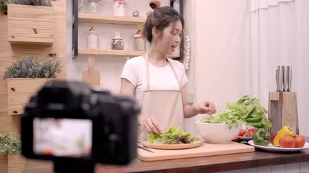 строгий вегетарианец : Blogger Asian woman using camera recording how to make salad healthy food video for her subscriber, female use organic vegetables preparing salad for fit body at home. Healthy food concept.