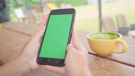 hírlevél : Young asian woman using black mobile phone device with green screen. Asian woman holding smartphone, scrolling pages while sitting in cafe. Chroma key.