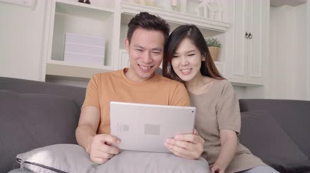 hozzábújva : Asian couple using tablet for online shopping in internet in living room at home, sweet couple enjoy love moment while lying on the sofa when relax at home. Lifestyle couple relax at home concept. Stock mozgókép