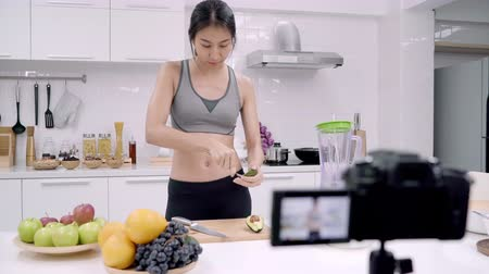 使用 : Blogger sporty Asian woman using camera recording how to make avocado juice video for her subscriber, female use organic fruit making avocado juice by herself at home. Healthy food concept. 動画素材