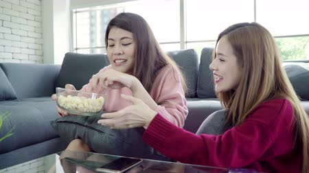 confortável : Asian women playing pillow fight and eating popcorn in living room at home, group of roommate friend enjoy funny moment while lying on the sofa. Lifestyle women relax at home concept.