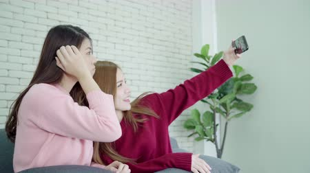 азиаты : Asians using smartphone selfie in living room at home