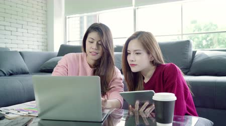 office life : Lesbian Asian couple using laptop making budget in living room at home, sweet couple enjoy love moment while lying on the sofa when relax at home. Lifestyle couple relax at home concept.