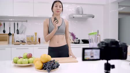 アボカド : Blogger sporty Asian woman using camera recording how to make avocado juice video for her subscriber, female use organic fruit making avocado juice by herself at home. Healthy food concept. 動画素材