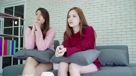 family watching tv : Lesbian Asian couple crying while watching drama in TV in living room at home, sweet couple enjoy romantic moment while lying on the sofa when relax at home. Lifestyle couple relax at home concept.