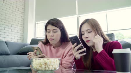 lesbian couple : Asian women using smartphone and eating popcorn in living room at home, group of roommate friend enjoy funny moment while lying on the sofa. Lifestyle women relax at home concept. Stock Footage