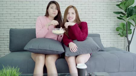 азиаты : Asians watching TV laugh and eating popcorn in living room at home, sweet couple enjoy funny moment while lying on the sofa when relax at home. Lifestyle couple relax at home concept. Стоковые видеозаписи