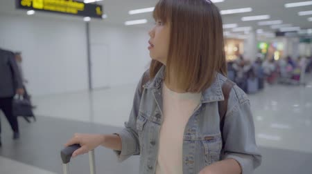klaar : Slow motion - Happy Asian woman using trolley or cart with many luggage walking in terminal hall while going to boarding flight at the departure gate in international airport. Stockvideo
