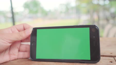 érintőképernyő : Young asian woman using black mobile phone device with green screen. Asian woman holding smartphone, scrolling pages while sitting in cafe. Chroma key.