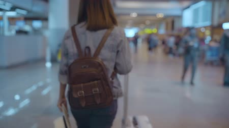 bavul : Slow motion - Happy Asian woman using trolley or cart with many luggage walking in terminal hall while going to boarding flight at the departure gate in international airport. Stok Video