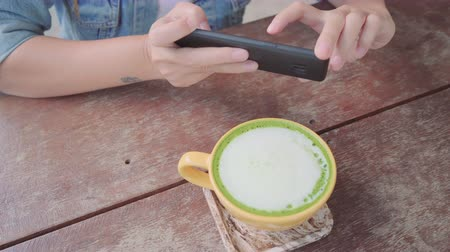 Female blogger photographing green tea cup in cafe with her phone. A young woman taking photo of coffee tea on smartphone, photographing meal with mobile camera. 影像素材