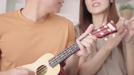 residencial : Asian couple playing guitar and singing together in living room at home, sweet couple enjoy love moment while lying on the sofa when relax at home. Lifestyle couple relax at home concept.