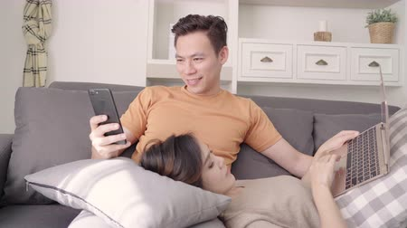 Asian couple using smartphone and laptop checking social media in living room at home, sweet couple enjoy love moment while lying on sofa when relaxed at home. Lifestyle couple relax at home concept. Wideo