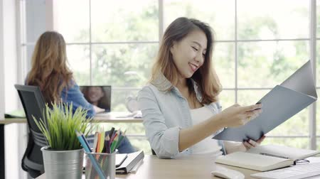 Asian business women working on computer while sitting on desk in smart casual wear at office, female working together in workplace. Lifestyle women work at office concept.