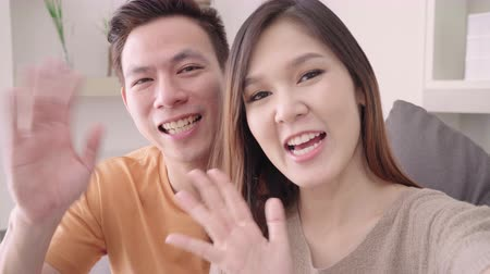 Asian couple using smartphone VIDEO Call with friend in living room at home, sweet couple enjoy love moment while lying on the sofa when relaxed at home. Lifestyle couple relax at home concept. 影像素材