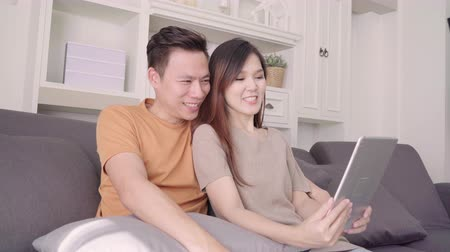 konferencja : Asian couple using tablet VIDEO Call with friend in living room at home, sweet couple enjoy love moment while lying on the sofa when relaxed at home. Lifestyle couple relax at home concept.