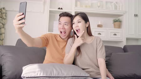 Asian couple using smartphone for selfie in living room at home, sweet couple enjoy love moment while lying on the sofa when relaxed at home. Lifestyle couple relax at home concept.