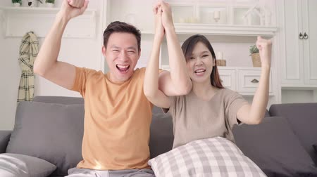 Asian couple cheer football match in front of television living room at home, sweet couple enjoy funny moment while lying on the sofa when relaxed at home. Lifestyle couple relax at home concept.