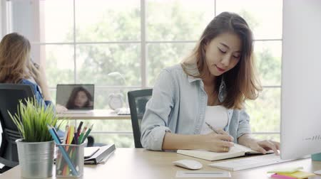 navegar : Asian Customer service women using computer answer customer e-mail on desk, female working on laptop while sitting on desk at office. Lifestyle women work at office concept. Stock Footage