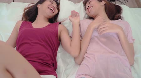 Slow motion - Young Asian women lesbian happy couple having fun in the morning after waking up in bedroom at home, enjoy love moment while lying on bed. Lifestyle LGBT couple together indoors concept.