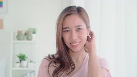 konferencja : Teenager Asian woman feeling happy smiling and looking to camera while relax in her bedroom at home. Beautiful Asian young female using relax time at home concept.