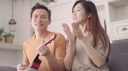 Asian couple playing guitar and singing together in living room at home, sweet couple enjoy love moment while lying on the sofa when relax at home. Lifestyle couple relax at home concept.