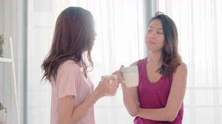 Young Asian women lesbian happy couple talking and drinking coffee in bedroom at home, enjoy love moment while lying on bed when relaxed in morning. Lifestyle LGBT couple together indoors concept. Wideo